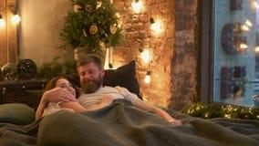 Pares felices que disfrutan de ocio en cama en la habitación metrajes