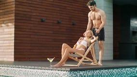 Pares felices que disfrutan del ocio del verano junto Hombre atractivo que toca a la muchacha cerca de piscina almacen de metraje de vídeo