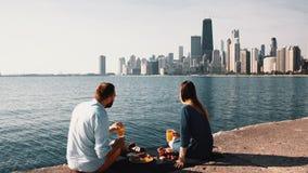 Pares felices que disfrutan del paisaje hermoso de Chicago, América en la orilla del lago michigan durante comida campestre almacen de metraje de vídeo
