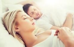 Pares felices que duermen en cama en casa Imagen de archivo