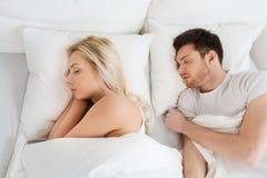 Pares felices que duermen en cama en casa Fotografía de archivo libre de regalías