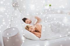 Pares felices que duermen en cama en casa Imagenes de archivo