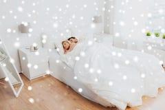 Pares felices que duermen en cama en casa Foto de archivo