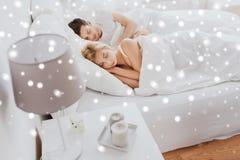 Pares felices que duermen en cama en casa Imagen de archivo libre de regalías