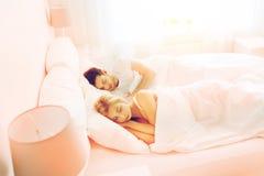 Pares felices que duermen en cama en casa Fotos de archivo libres de regalías