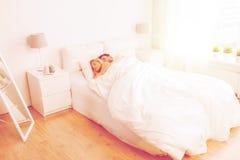 Pares felices que duermen en cama en casa Fotos de archivo