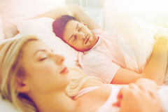 Pares felices que duermen en cama en casa Fotografía de archivo
