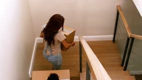 Pares felices que entran en su nuevo hogar con la caja móvil almacen de video