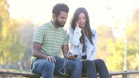 Pares felices que escuchan la música junto, compartiendo los auriculares metrajes