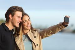 Pares felices que fotografían un selfie con el teléfono elegante Imagenes de archivo