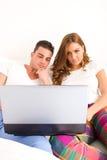 Pares felices que gozan con el ordenador portátil en cama imágenes de archivo libres de regalías