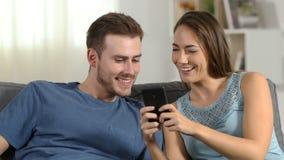 Pares felices que hablan del contenido del teléfono en casa metrajes