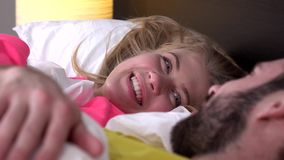 Pares felices que hablan por la mañana en una cama cómoda en casa, primer almacen de metraje de vídeo