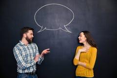 Pares felices que hablan sobre fondo de la pizarra con diálogo exhausto Imagen de archivo
