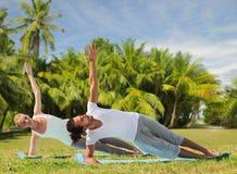 Pares felices que hacen ejercicios de la yoga en la playa Fotos de archivo