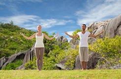 Pares felices que hacen ejercicios de la yoga en la playa Imagen de archivo libre de regalías