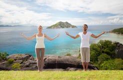 Pares felices que hacen ejercicios de la yoga en la playa Fotografía de archivo