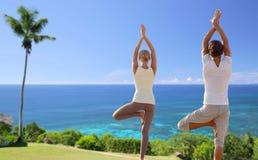 Pares felices que hacen ejercicios de la yoga en la playa Foto de archivo