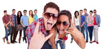 Pares felices que hacen el gesto del rock-and-roll Foto de archivo libre de regalías