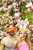 Pares felices que hacen el selfie en smartphone en los ?rboles florecientes de la magnolia imagen de archivo