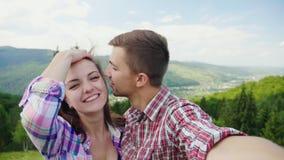 Pares felices que hacen el selfie en un fondo de montañas hermosas Vacaciones magníficas y vacaciones cámara lenta 4k