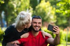Pares felices que hacen el selfie usando smartphone Imágenes de archivo libres de regalías