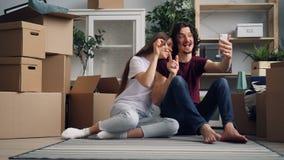 Pares felices que hacen la llamada video con smartphone después de sonreír que habla de la relocalización almacen de video