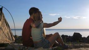Pares felices que hacen selfies en la costa cerca de la tienda almacen de metraje de vídeo