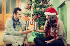 Pares felices que intercambian los regalos en casa por el árbol de navidad fotografía de archivo libre de regalías