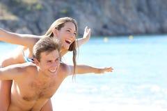 Pares felices que juegan en la playa Foto de archivo