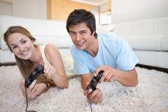 Pares felices que juegan a los videojuegos Imagen de archivo libre de regalías