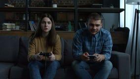 Pares felices que juegan a los videojuegos en la consola almacen de metraje de vídeo