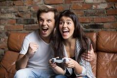 Pares felices que juegan a los videojuegos juntos en casa foto de archivo