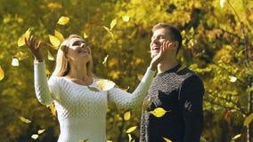 Pares felices que lanzan para arriba las hojas de otoño, amor sincero y sensaciones románticas almacen de metraje de vídeo