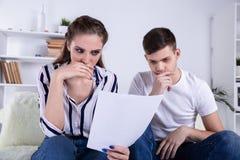 Pares felices que leen el correo y que comprueban la contabilidad que se mira que se sienta en un sof? imagen de archivo