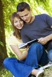 Pares felices que leen un libro al aire libre Imagen de archivo libre de regalías
