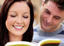 Pares felices que leen un libro junto Fotografía de archivo