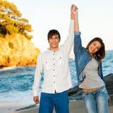 Pares felices que levantan los brazos en la playa. Fotos de archivo libres de regalías