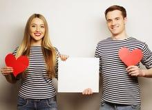 Pares felices que llevan a cabo el espacio en blanco blanco Imágenes de archivo libres de regalías