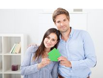 Pares felices que llevan a cabo el modelo de la casa verde Fotografía de archivo libre de regalías