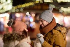 Pares felices que llevan a cabo las manos en el mercado de la Navidad fotos de archivo