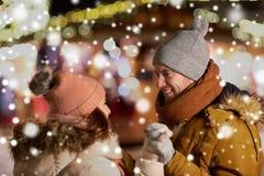Pares felices que llevan a cabo las manos en el mercado de la Navidad imagenes de archivo