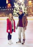 Pares felices que llevan a cabo las manos en pista de patinaje Imágenes de archivo libres de regalías