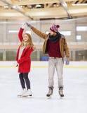 Pares felices que llevan a cabo las manos en pista de patinaje Imagenes de archivo