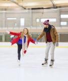 Pares felices que llevan a cabo las manos en pista de patinaje Foto de archivo
