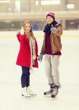 Pares felices que llevan a cabo las manos en pista de patinaje Foto de archivo libre de regalías