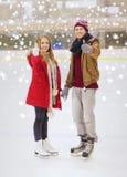 Pares felices que llevan a cabo las manos en pista de patinaje Imagen de archivo libre de regalías