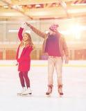 Pares felices que llevan a cabo las manos en pista de patinaje Fotos de archivo