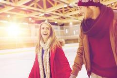 Pares felices que llevan a cabo las manos en pista de patinaje Fotografía de archivo libre de regalías