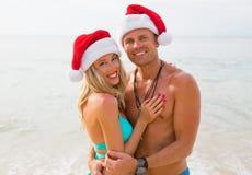 Pares felices que llevan los sombreros de Papá Noel en la playa Fotos de archivo